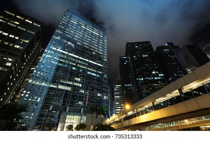 Night cityscape with skyscrapers under dark cloudy sky, high-rise office buildings in Hong Kong city