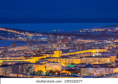 Night cityscape. Top view of the port town. Bright street lighting at dusk. In the distance sea bay. Magadan, Siberia, Far East of Russia. Coast of the Sea of Okhotsk.