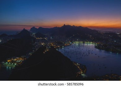 Night Cityscape view from the Sugarloaf mountain in Rio de Janeiro, Brazil. Guanabara bay, Botafogo, Flamengo and Urca districts, Atlantic ocean, Corcovado mountain with Christ the Redeemer.