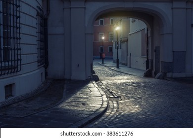 night cityscape in warsaw; narrow historic street with an arch and street lamps