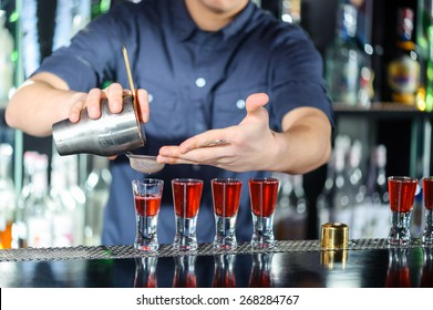 Night club. Barman using a shake mixer cocktails and drinks in nightclub, bar or pub