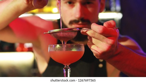 Night club. The bartender pours a cocktail through a sieve into a glass.