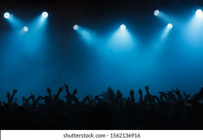 Night club dj concert crowds waving hands in blue stage lights.Silhouette of edm musical festival crowd partying on dancefloor.Illuminated scene in music hall.Background for entertainment event poster