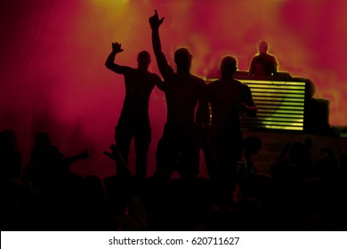Night club dj party people enjoy of music dancing sound with colorful light with Smoke Machine and lights show. Hands up in the earth. Audience on concert in night club. Dark background.