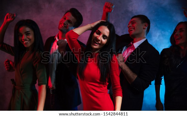 A night in the club. A group of five young people with extremely happy face expressions, wearing dresses and suits, are dancing together at the party in the club.