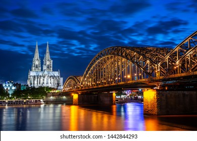 Night in Cologne at the river Rhine with the illuminated cathedral and the Hohenzollern Bridge.