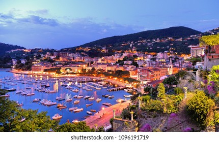 night colorful boats and seascape with old castle and blue cloudy sky in Lerici in Liguria, Italy