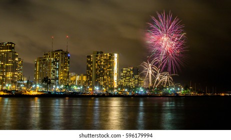 Night colorful fireworks at beach with reflection in water, captured at Magic Island, Honolulu.