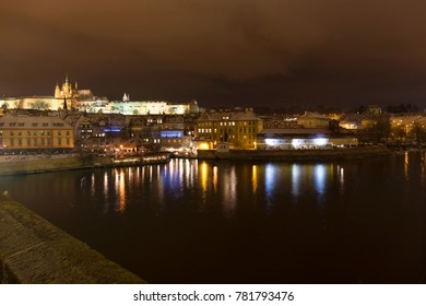 Night colorful snowy Christmas Prague Lesser Town with gothic Castle from Charles Bridge, Czech republic