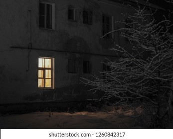 Night. The dark wall of the house. The light from the window. Winter, snow, wood