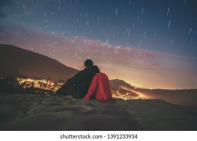 The night desert view of Huacachina, Ica, Peru. A couple sit on the ground and admire the beautiful night view.