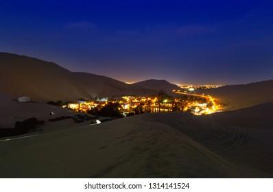 The night desert view of Huacachina oasis, Ica, Peru .