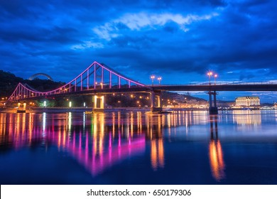 Night european city in colorful lights and reflection in water, Kyiv (Kiev) the capital of Ukraine. Pedestrian bridge across the Dnieper river and view to the river station