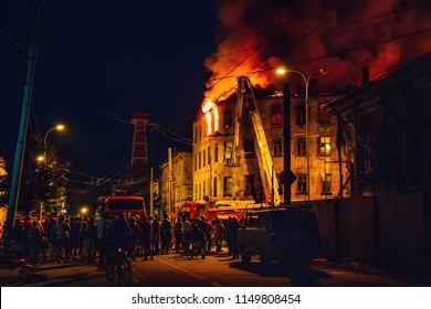 Night fire in apartment building, firefighters struggle with flame, silhouettes of unrecognizable people stand around. Fire disaster and accident tragedy concept, toned