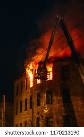 Night fire in burning apartment building, firefighters struggle with flame. Fire disaster and accident tragedy concept