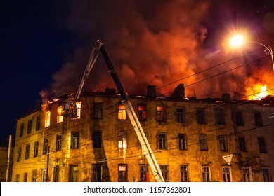 Night fire at roof in apartment building, burning house with huge smoke, Fire disaster and accident tragedy concept