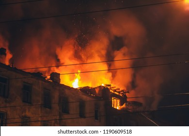 Night fire at roof in building, burning house with smoke, Fire disaster and accident tragedy concept