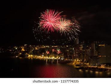 Night fireworks over the light city