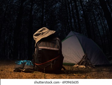 Night forest with backpack gear and clothing. Backpack with travel gear, bucket hat, flashlight, sneakers and travel tent on dark forest night landscape background.
