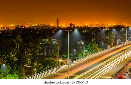 Night freeway with car traffic, lights trails and city lights when long exposed.