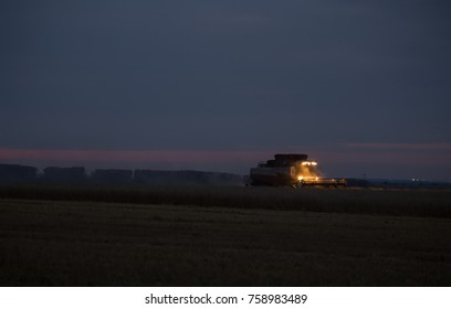 night harvesting in the fields. Combines with lights in motion in the late evening.