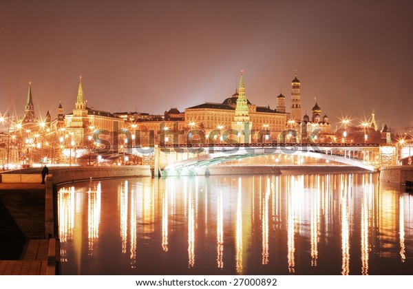 A night hdr view of the Moscow city Kremlin with an illuminated river and a bridge