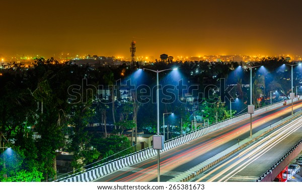 Night highway with car traffic, lights trails and city lights when long exposure, soft focus