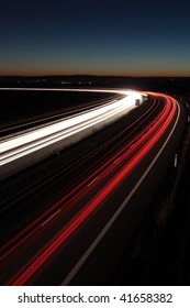 Night highway (Cars in a rush moving fast on a highway (speedway) at the nightfall