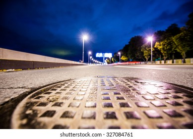 Night highway, the glowing lights of approaching car. Wide angle view of the level of a manhole on the pavement, in blue tones
