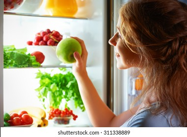 night hunger. Woman in the dark at the open refrigerator