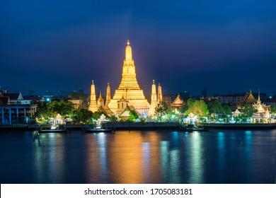 Night illuminated Temple of Dawn or Wat Arun and its reflection in Chao Phraya River at sunset. Bangkok, Thailand