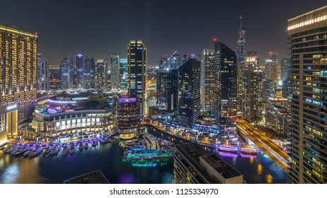 Night illumination of Dubai Marina aerial timelapse, UAE. Modern skyscrapers and residential buildings. Traffic on the road. Yachts and boats near shoping mall on artificial canal city