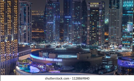 Night illumination of Dubai Marina and JLT aerial timelapse, UAE. Modern skyscrapers and residential buildings. Traffic on the road. Swimming pool on rooftop