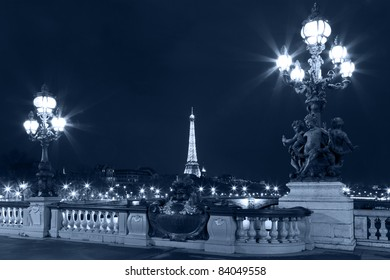 Night illumination on the bridge of Alexander III and Eiffel Tower in the background. Paris. France.