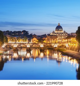 Night image of River Tiber, including: Ponte Sant Angelo and St. Peter's Basilica in the background. Rome - Italy