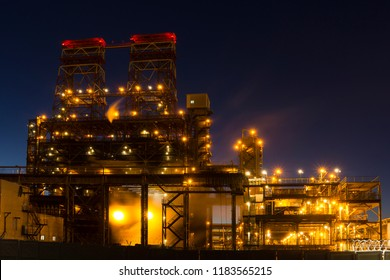 Night industrial landscape with bright lights of lanterns - 4-drum delayed coking unit in a petroleum refinery