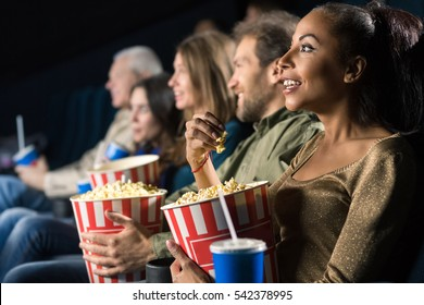 Night of joy. Beautiful African woman holding her popcorn bucket smiling joyfully while watching a movie at the cinema with her friends copyspace