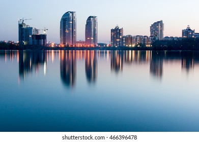 Night Kiev over the river. Reflection of the city in the evening water of the river