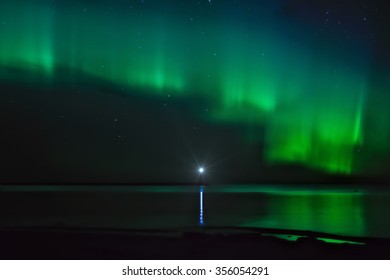 Night landscape with Aurora Borealis over the Ladoga Lake and a lighthouse