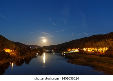 night landscape at Bad Schandau, Saxony, Germany with full moon reflecting on river elbe
