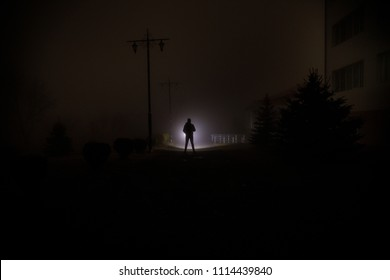Night Landscape. City at night in dense fog. Mystical landscape surreal lights with creepy man. The walking man's silhouette in night fog at artificial light. Beautiful mixed lighting from backside.