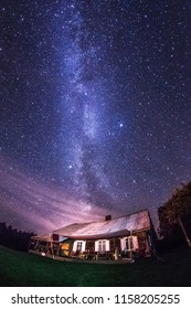 Night landscape with colorful Milky Way stars over the trees and coutry home outside the city. Starry sky with home at summer. Beautiful Universe. Space astro photography background