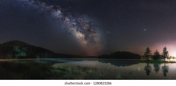 Night landscape with colorful Milky Way and light at mountains. Starry sky with hills at summer. Beautiful Universe. Lake in front. Space background, shot from Bulgaria