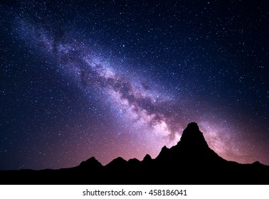 Night landscape with colorful Milky Way and mountain peak. Starry sky with high rocks at summer. Beautiful Universe. Space background. Travel