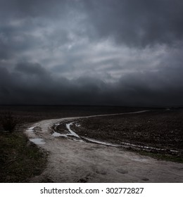 Night Landscape with Country Road and Dark Clouds. Moody Sky Background.