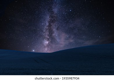 Night landscape with field on hills and Milky way sky
