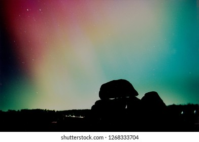 Night landscape illuminated by Aurora Borealis, The silhouette of a bronze age barrow make out the foreground.