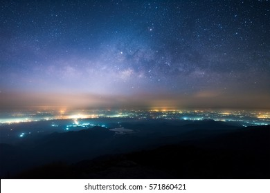 Night landscape of Milky way above the light of countryside area and mountain.