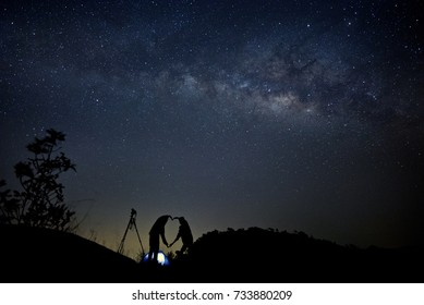 Night landscape with Milky Way and silhouette of people. Night starry sky with silhouette of happy friends holding hands in heart shape on the mountain. Beautiful Universe. Astrophotography