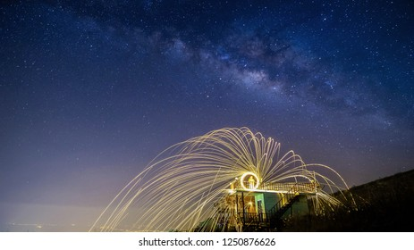 night landscape mountain and Wield the fire , milkyway galaxy background , long exposure ,low light
